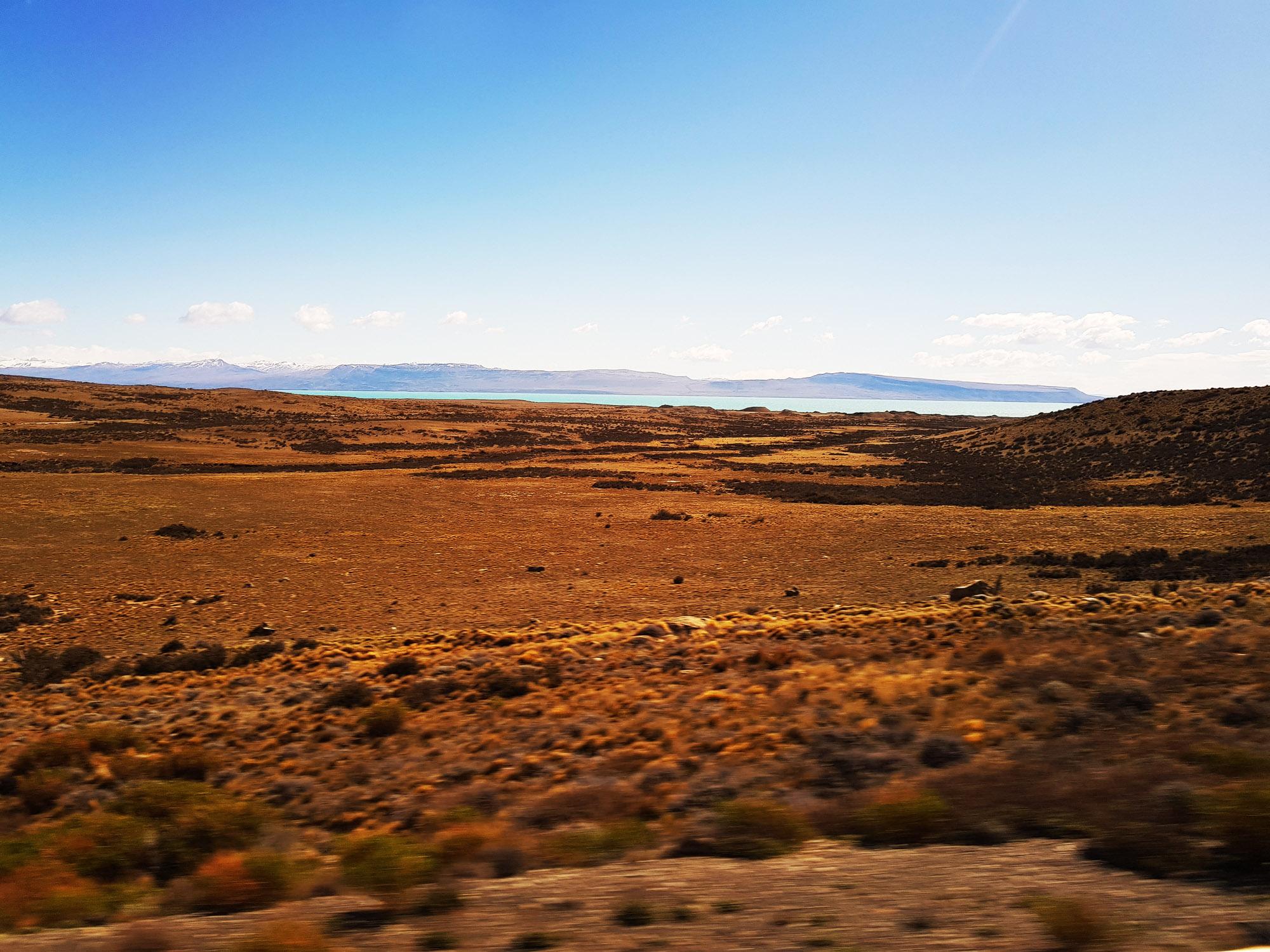 12.30 Uhr: Pampa, aber in der Ferne schon Wasser und Berge